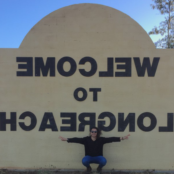 JCU Physio student, Mason in front of the Welcome to Longreach sign